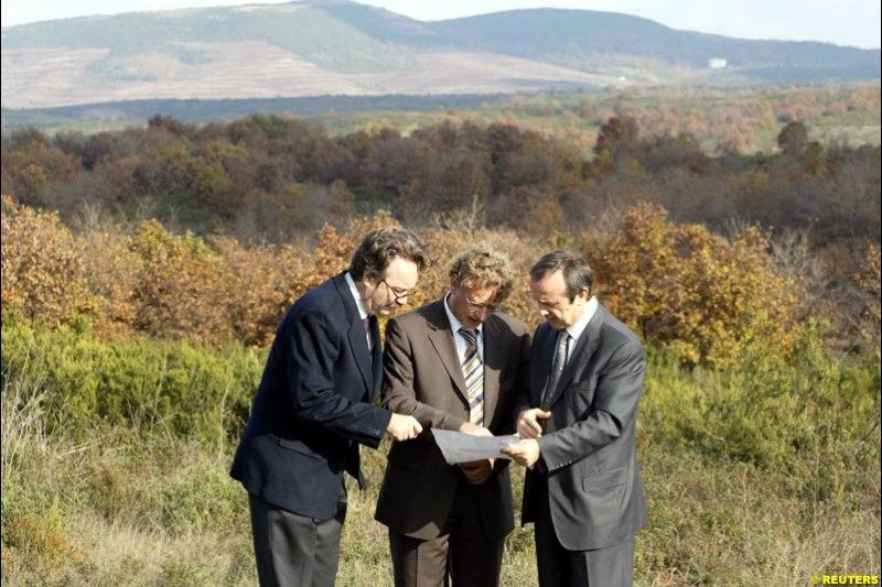 Formula One race track architect Hermann Tilke (center), flanked by Turkey's car and motor sports association chairman Mumtaz Tahincioglu (right) and an official from Turkish F1 committee Mehmet Karabeyoglu (left), looks at a map as he inspects a field on which a future track may be built for a Formula One Grand Prix in Istanbul November 26, 2002.
