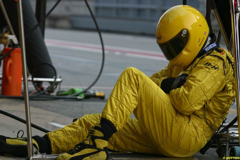 Jordan mechanic takes a rest during testing at Barcelona, Spain. 18th February 2003.