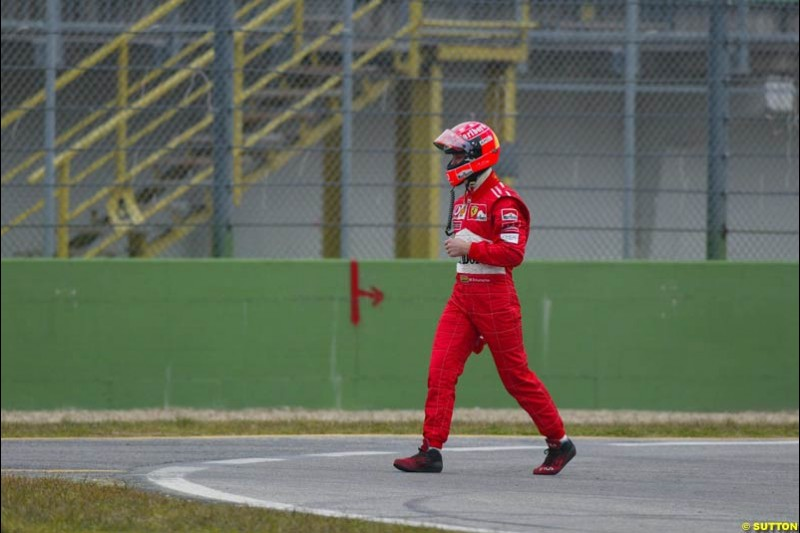 Michael Schumacher walks back to the pits after his Ferrari F2003-GA broke down during testing at the Imola circuit in Italy. 17th February, 2003.