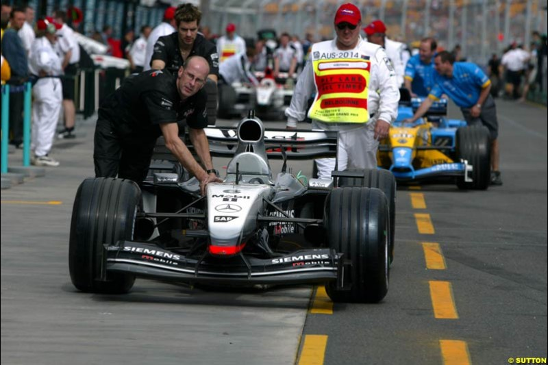 McLaren push their car back to the garage under the supervision of the scrutineers, after qualifying for the Australian GP. Melbourne, March 8th 2003.
