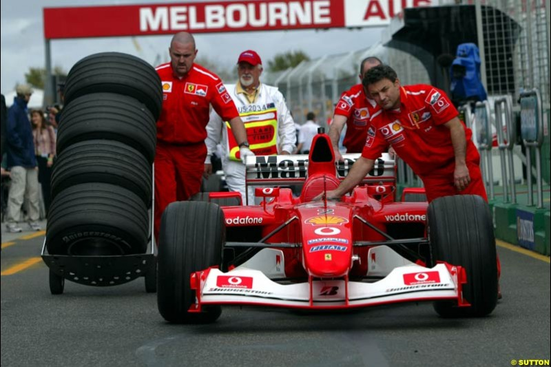 The Ferrari crew bring back the car to the garage under the supervision of the scrutineer after qualifying for the Australian GP. Melbourne, March 8th 2003.