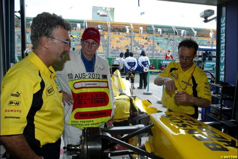 The official race scrutineers oversee the Jordan cars, with team boss Eddie Jordan looking, before they are locked in parc ferme. Australian GP, Melbourne, March 8th 2003.