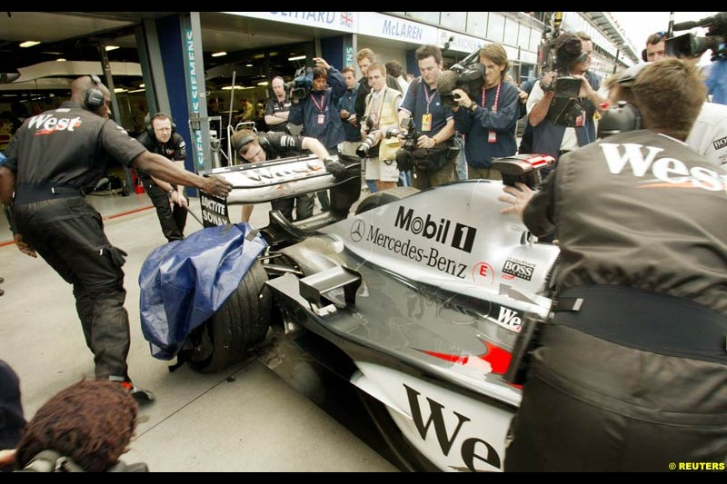 David Coulthard's McLaren is wheeled back into the team garage after he blew a tyre during Saturday practice for the Australian GP. Melbourne, March 8th 2003.