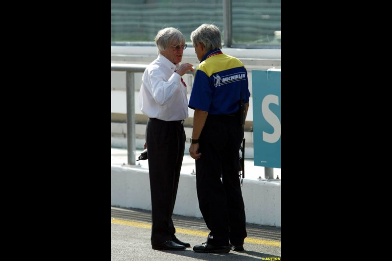 Bernie Ecclestone with Pierre Dupasquier, Michelin, during Friday morning testing at Sepang International Circuit. Malaysian GP, March 21st 2003.