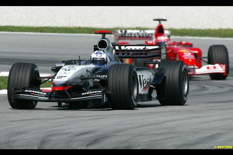 David Coulthard, McLaren, followed by Rubens Barrichello, Ferrari, during Saturday practice for the Malaysian GP. Sepang, March 22nd 2003.
