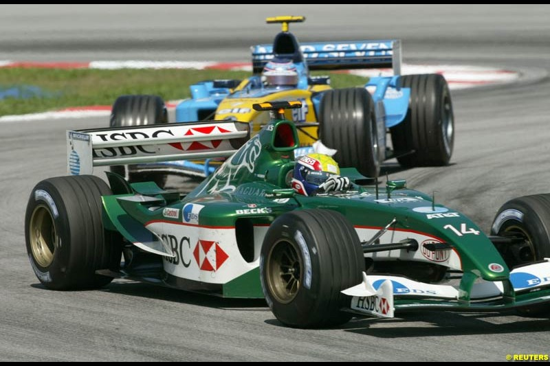 Mark Webber, Jaguar, followed by Jarno Trulli, Renault, during Saturday practice for the Malaysian GP. Sepang, March 22nd 2003.