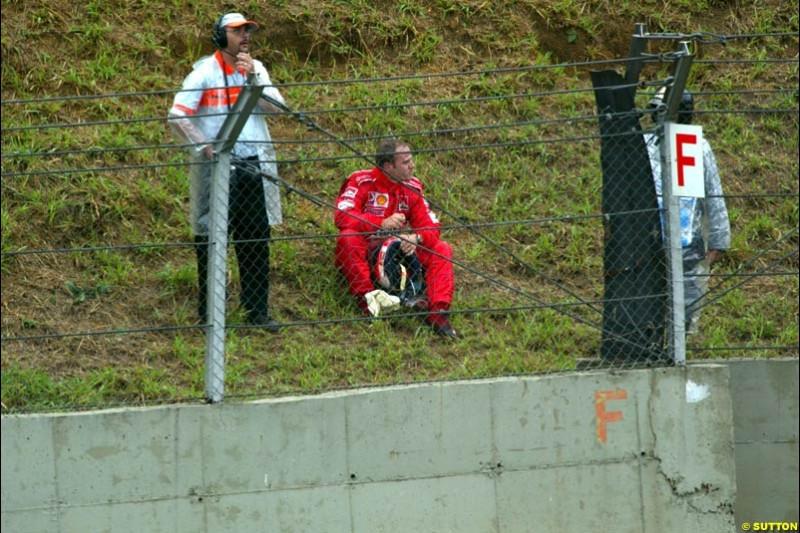 Rubens Barrichello, Ferrari, sits after failing to finish the race. Brazilian Grand Prix. Interlagos, Sao Paulo, April 6th 2003.