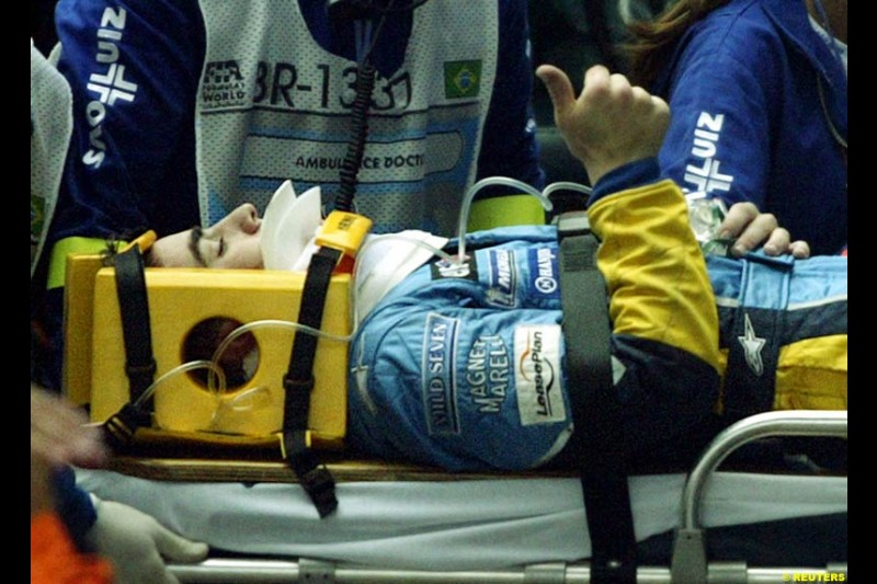 Fernando Alonso, Renault, gives a thumbs up after suffering a heavy accident that caused the race to be halted. Brazilian Grand Prix. Interlagos, Sao Paulo, April 6th 2003.