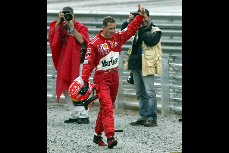 Michael Schumacher, Ferrari, walks back to the pits after spinning out. Brazilian Grand Prix. Interlagos, Sao Paulo, April 6th 2003.