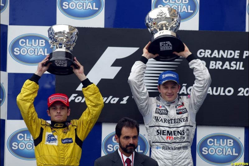 Kimi Raikkonen, McLaren, 1st, celebrates with Giancarlo Fisichella, Jordan, 2nd. Absent is Fernando Alonso, Renault, who required post race medical attention. Brazilian Grand Prix. Interlagos, Sao Paulo, April 6th 2003.