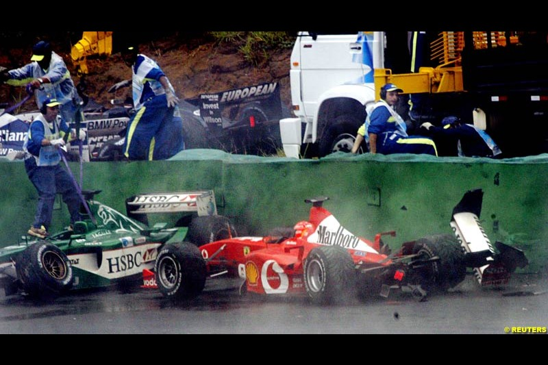 Wet conditions catch out Michael Schumacher, Ferrari, who joined a collection of cars that had fallen foul of turn 3. Brazilian Grand Prix. Interlagos, Sao Paulo, April 6th 2003.