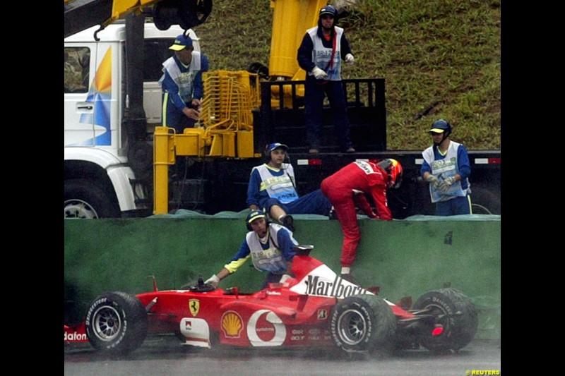 Michael Schumacher, Ferrari, climbs over the barriers after crashing out of the Brazilian Grand Prix. Interlagos, Sao Paulo, April 6th 2003.