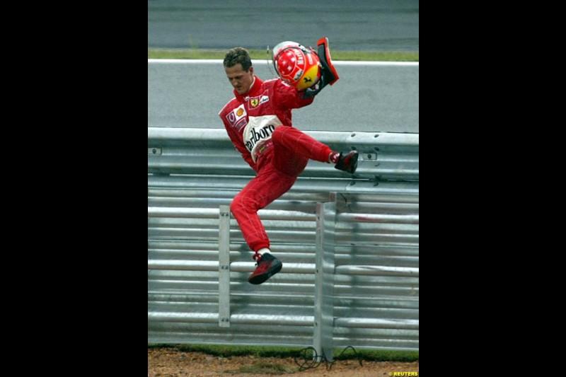 Michael Schumacher, Ferrari, jumps a barrier after crashing out of the Brazilian Grand Prix. Interlagos, Sao Paulo, April 6th 2003.