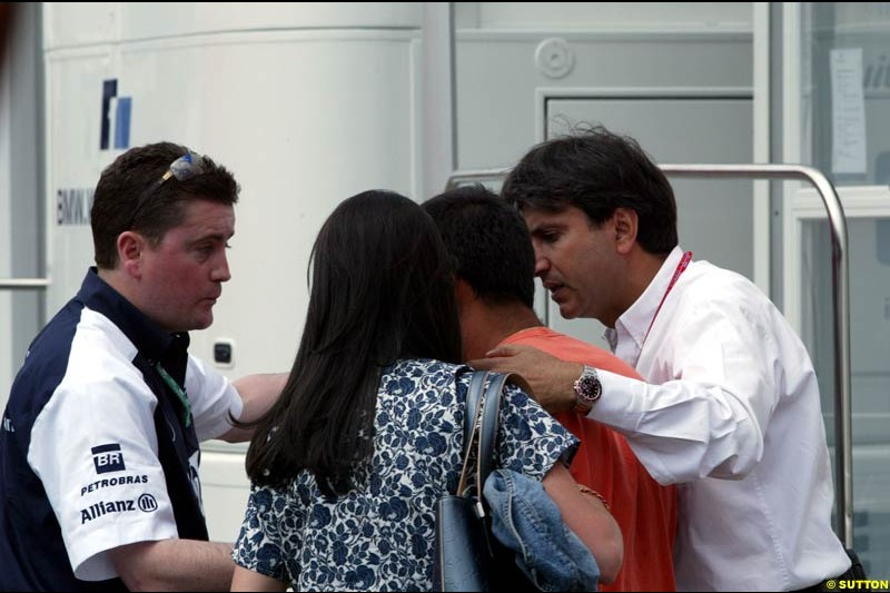 A Williams team Member, Connie Montoya and Pasquale from the FIA help calm down Juan Pablo Montoya after he was hit on the head by a TV camera in a media scrum at the Imola circuit, Italy. 17th April, 2003.