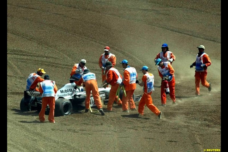 Marshals recover the car of David Coulthard, McLaren. Spanish Grand Prix. Circuit de Catalunya, Barcelona, Spain. May 4th 2003.