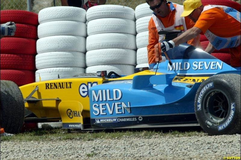 Jarno Trulli's Renault sits in the gravel after a first lap accident. Spanish Grand Prix. Circuit de Catalunya, Barcelona, Spain. May 4th 2003.