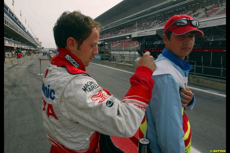 Cristiano Da Matta, Toyota, signs an autograph on the back of a pit lane marshal. Sunday, Spanish Grand Prix, Circuit de Catalunya. Barcelona, Spain, May 4th 2003.