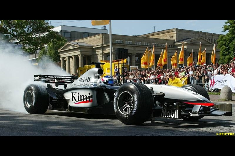 Kimi Raikkonen drives his McLaren Mercedes in Stuttgart's inner city to present his F1 car at the 100th anniversary of the General German Automobile Association (ADAC). May 24, 2003.