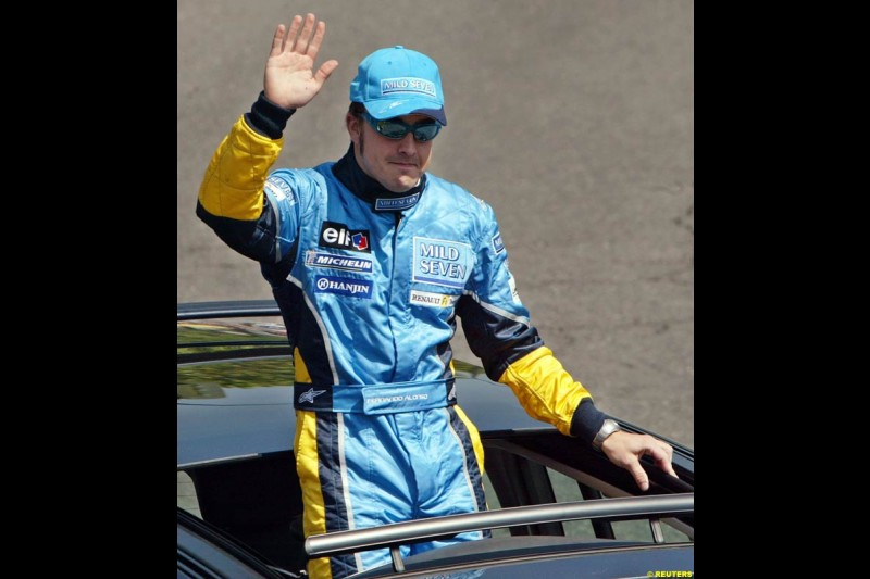 Renault's Fernando Alonso salutes the crowd after driving down Madrid's central Paseo de la Castellana during an exhibition celebrating his success so far this season. May 11th 2003.