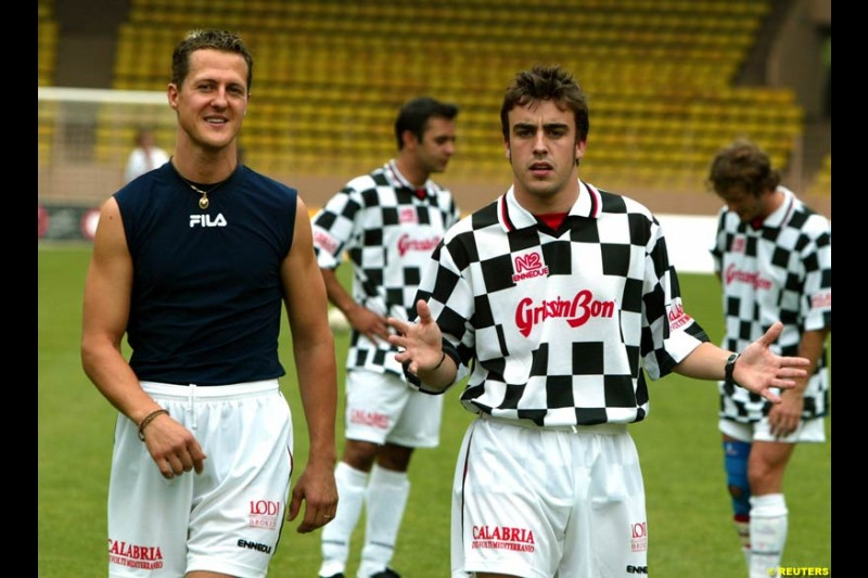 Michael Schumacher chats with Fernando Alonso before a soccer match between the and quot;Star Team for Children and quot; and Formula One drivers in Monaco May 27, 2003. The event was set up for the benefit of A.M.A.D.E, a charity which helps children all around the world.