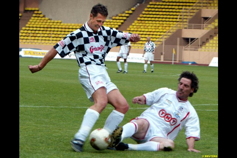 Michael Schumacher challenges french goalkeeper Jean Luc Ettori during a soccer match between the Star team for children and Formula One drivers in Monaco May 27, 2003. The event was set up for the benefit of A.M.A.D.E, a Monegasque association which helps children all around the world