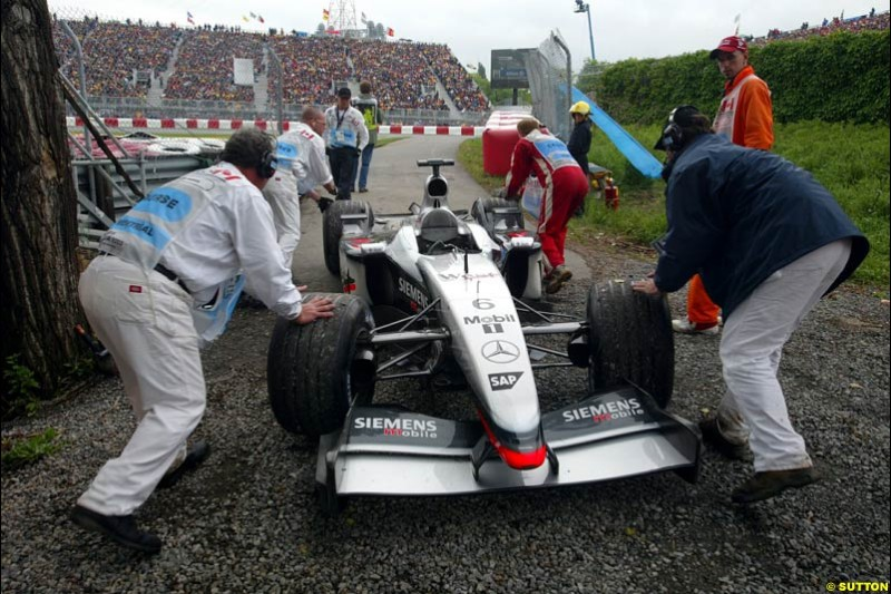 Marshals attend to the car of Kimi Raikkonen, McLaren, during qualifying. Canadian Grand Prix, Montreal, Saturday, June 14th 2003.