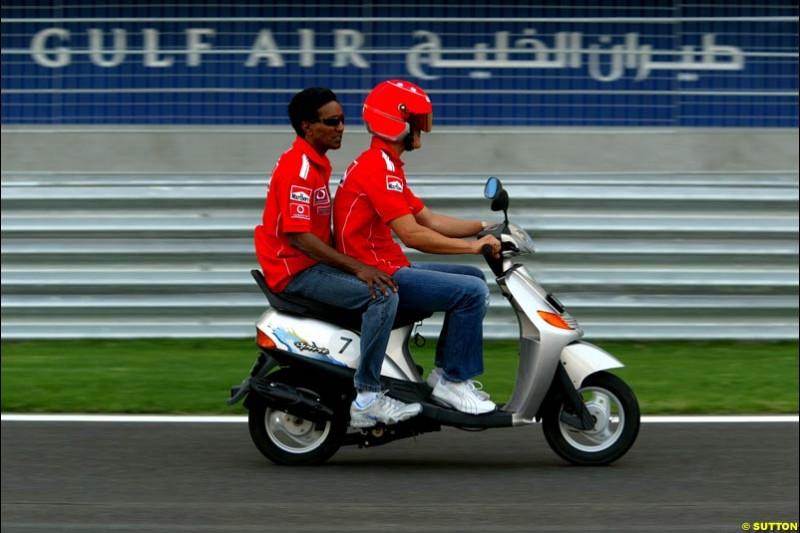 Michael Schumacher rides around the circuit on his scooter. Bahrain Grand Prix, Bahrain International Circuit. April 1st, 2004.