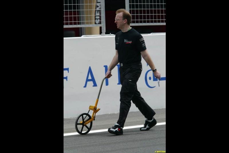 A McLaren mechanic measures the pitlane. Bahrain Grand Prix, Bahrain International Circuit. April 1st, 2004.