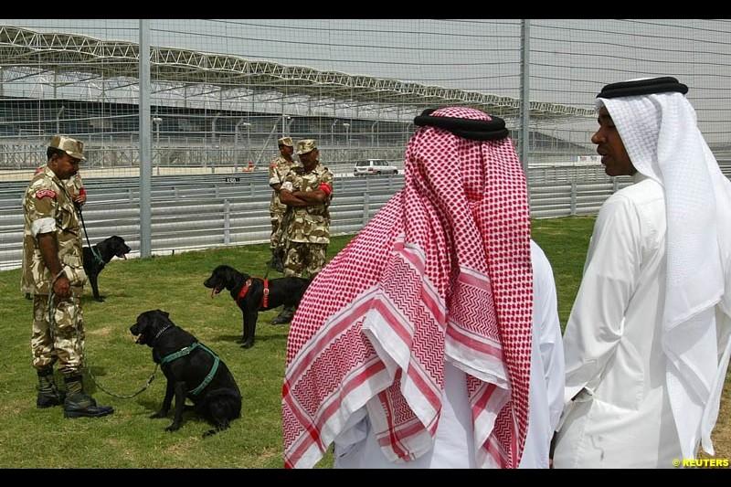 Two Bahrainis watch a training session of a dog squad. Bahrain Grand Prix, Bahrain International Circuit. April 1st, 2004.