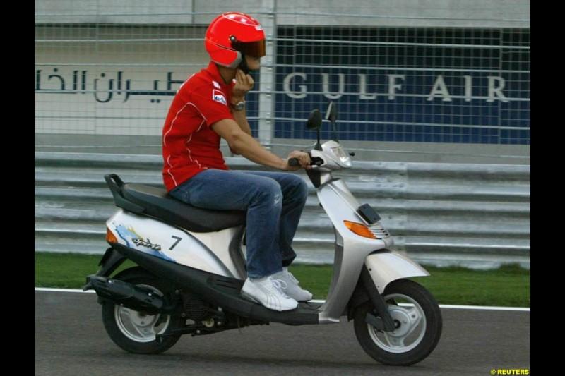Michael Schumacher drives around the circuit on his scooter. Bahrain Grand Prix, Bahrain International Circuit. April 1st, 2004.