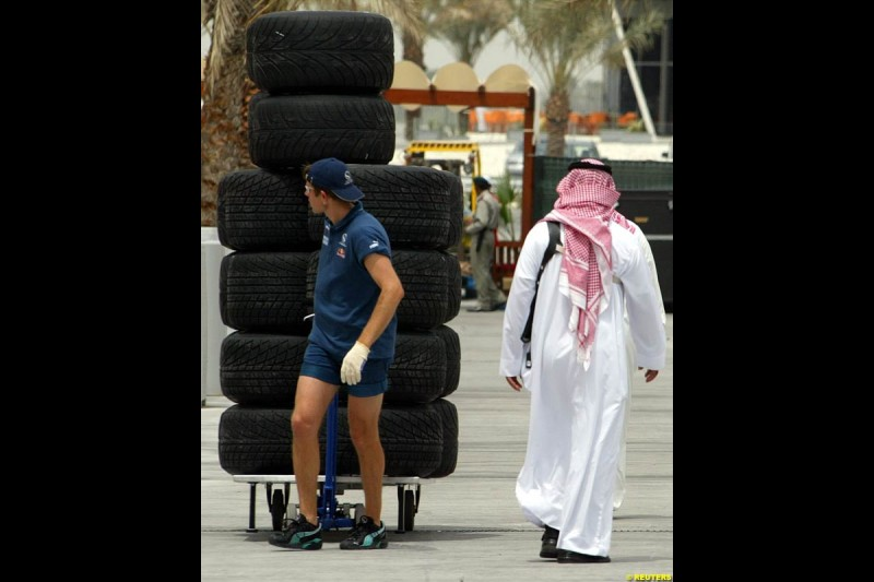 Sauber mechanic pulls a rack of tires as locals take a walk in the pitlane of the Bahrain International Circuit near the Bahrain capital of Manama, ahead of the first Bahrain Grand Prix. March 31st, 2004.