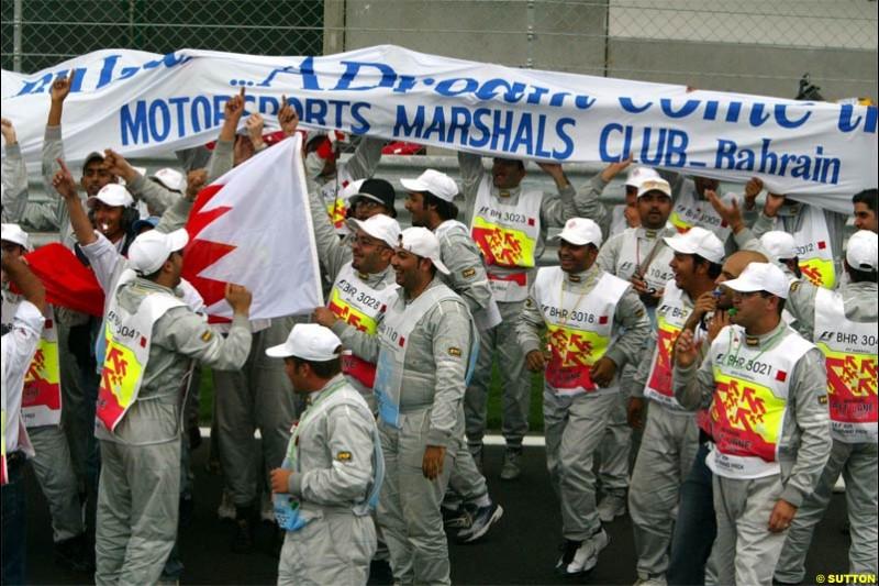 The track's marshals celebrate a job well done. The Bahrain Grand Prix. Bahrain International Circuit, April 4th 2004.