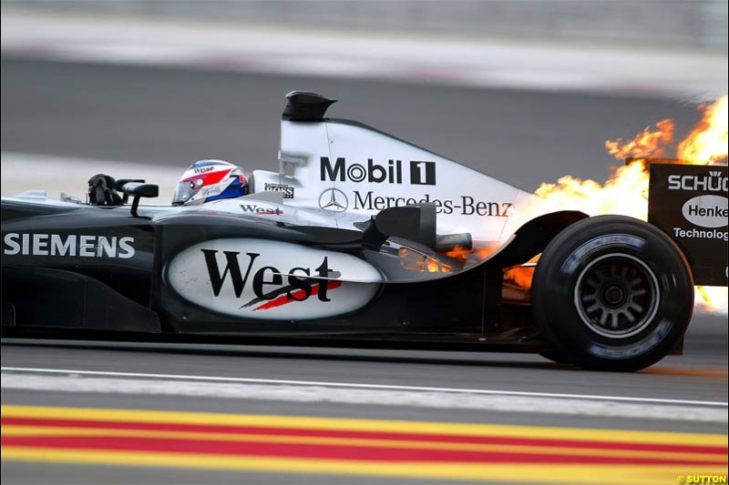 Fire erupts from the back of Kimi Raikkonen, McLaren, after a failure. The Bahrain Grand Prix. Bahrain International Circuit, April 4th 2004.