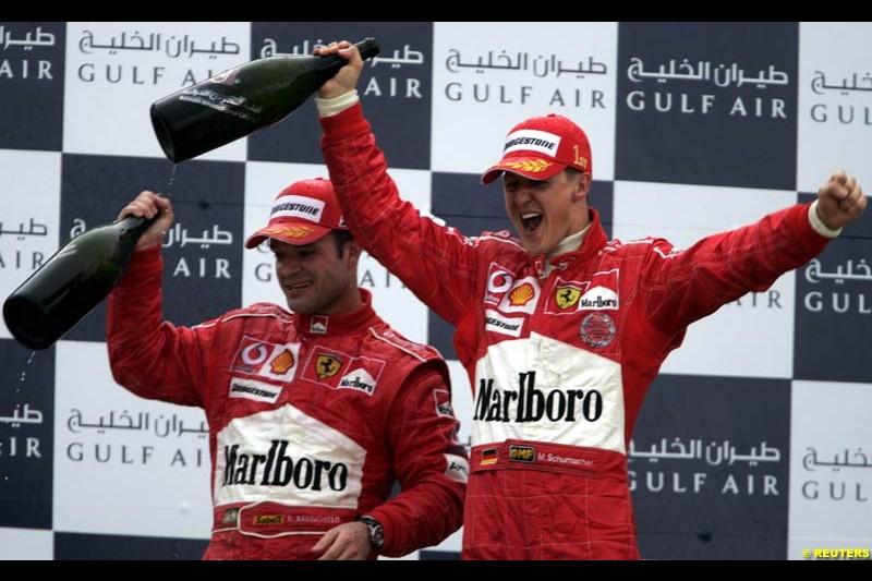 Rubens Barrichello and Michael Schumacher celebrating on the podium. The Bahrain Grand Prix. Bahrain International Circuit, April 4th 2004.