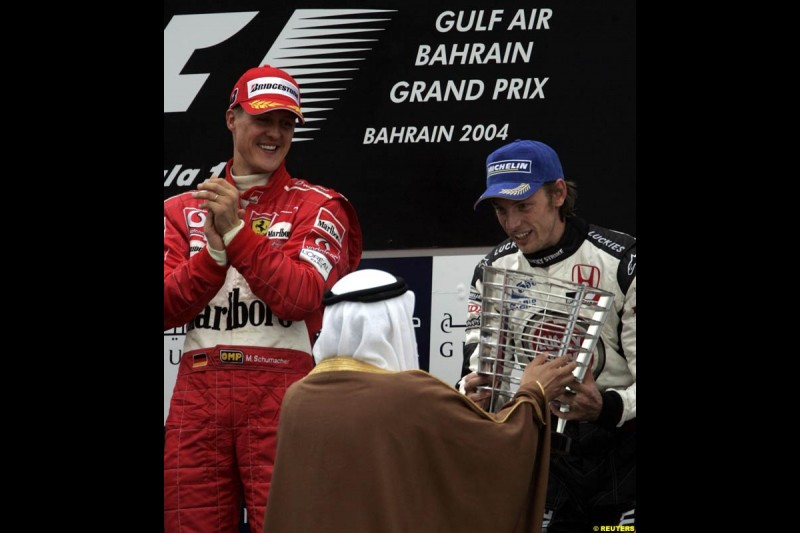 Michael Schumacher looks at Jenson Button as he receives his trophy for third place. The Bahrain Grand Prix. Bahrain International Circuit, April 4th 2004.