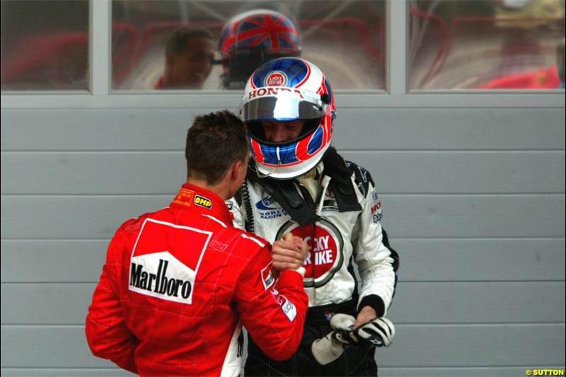Michael Schumacher, Ferrari, and Jenson Button, BAR, exchange congratulations. The Bahrain Grand Prix. Bahrain International Circuit, April 4th 2004.