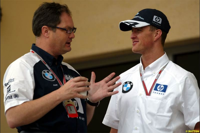 Ralf Schumacher, Williams, talks to Frank Dernie, Williams Head of Special Projects. Race Day for the Bahrain Grand Prix. Bahrain International Circuit, April 4th 2004.