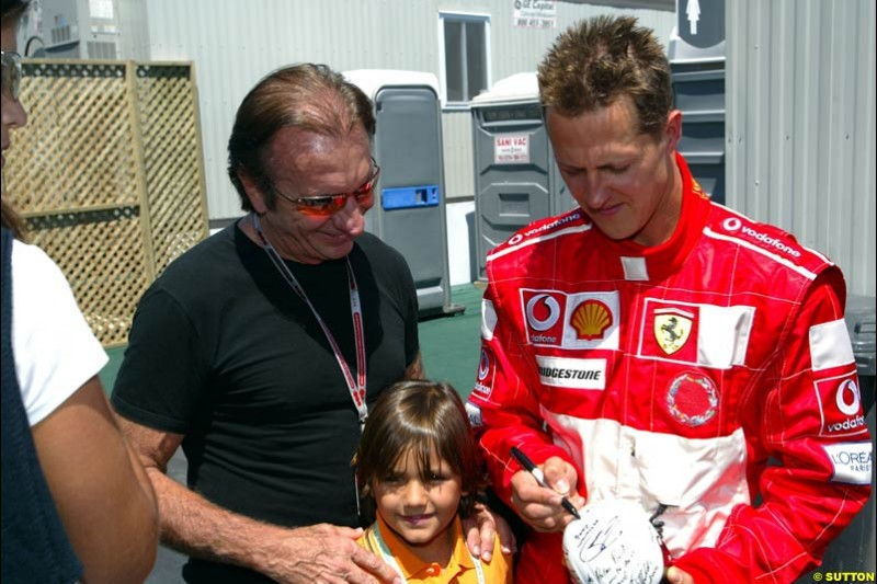 Former World Champion Emerson Fittipaldi gets an autograph for his son from Michael Schumacher, Ferrari, after qualifying. The Canadian Grand Prix, Montreal, Canada. Saturday, June 13th, 2004.