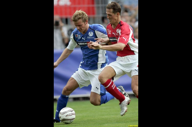 Michael Schumacher challenges ski-jumper Georg Spaeth during a charity soccer match in Mannheim, July 21, 2004.