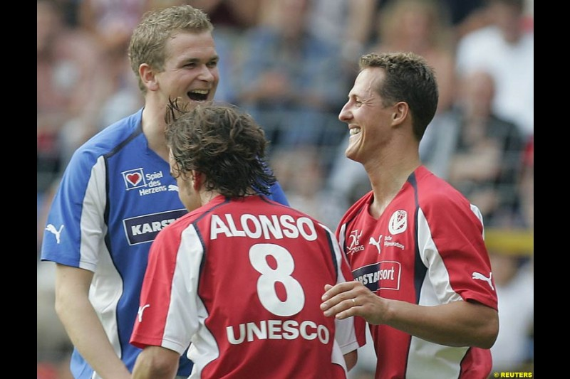 Michael Schumacher celebrates his penalty goal with Fernando Alonso during a charity soccer match in Mannheim, July 21, 2004.
