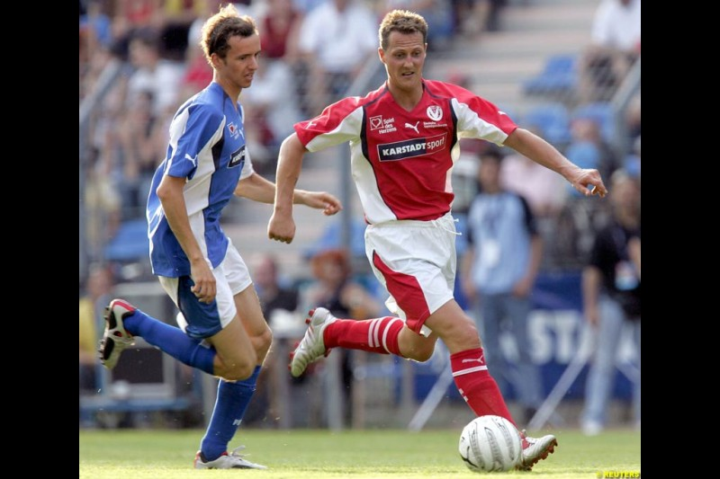 Michael Schumacher challenges German talkmaster Oliver Geissen during a charity soccer match in Mannheim, July 21, 2004.
