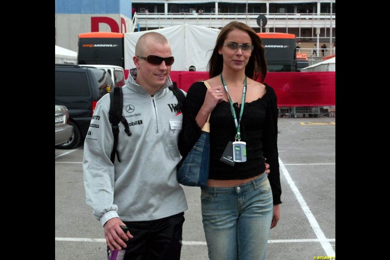 Kimi Raikkonen, sporting a new hair-do (or none, for that matter), leaves the paddock after the race with his girlfriend. Barcelona, Spain. April 28th 2002.
