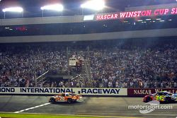 Tony Stewart passe sous le drapeau à damier devant Jeff Gordon