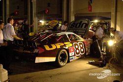 El equipo de Dale Jarrett trabaja bajo las luces de un generador de poder luego de que se fuera la l