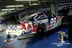 El golpeado Ford Taurus de Jeff Burton yace solo en el área de garage luego de que el equipo sacara