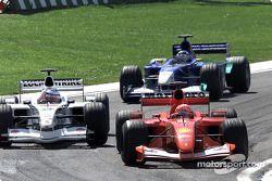 Michael Schumacher passing Olivier Panis, with Kimi Raikkonen watching