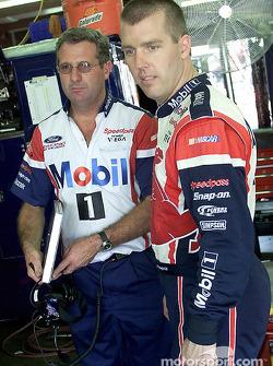Jeremy Mayfield y el jefe de equipo, Peter Sospenzo, discuten la puesta a punto del auto en el área del garage