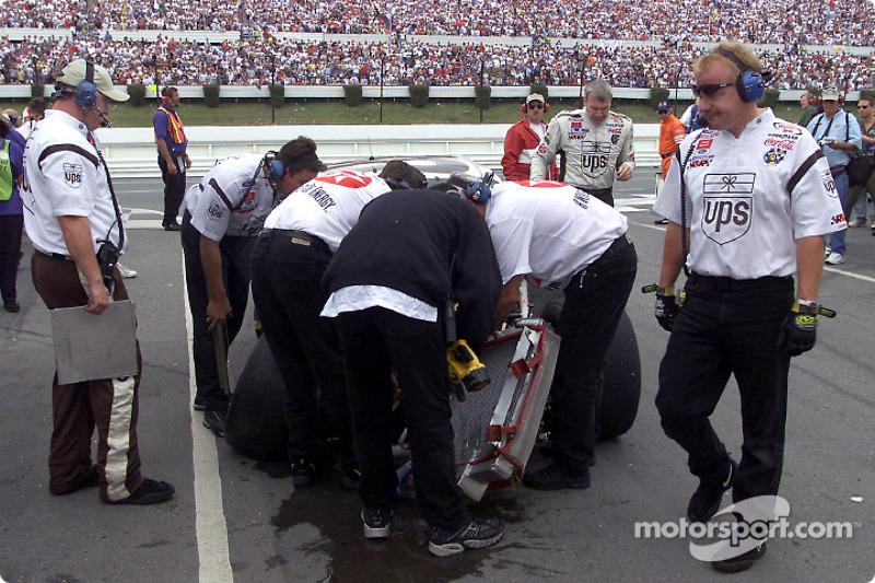 Dale Jarrett sale de su accidentado Ford Taurus UPS mientras el equipo analiza los daños