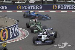 Juan Pablo Montoya in front of Eddie Irvine and Luciano Burti