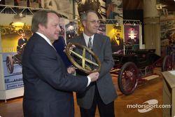 Dan Davis, directeur de Ford Racing Technologies, présente un volant commémoratif à Edsel B. Ford II, durant une cérémonie dévoilant la Ford Sweepstakes de 1901 au musée Henry Ford